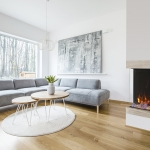 Wooden table on round rug near sofa in spacious living room interior with fireplace and painting