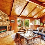 Luxury log cabin house interior. Living room with fireplace and leather couch
