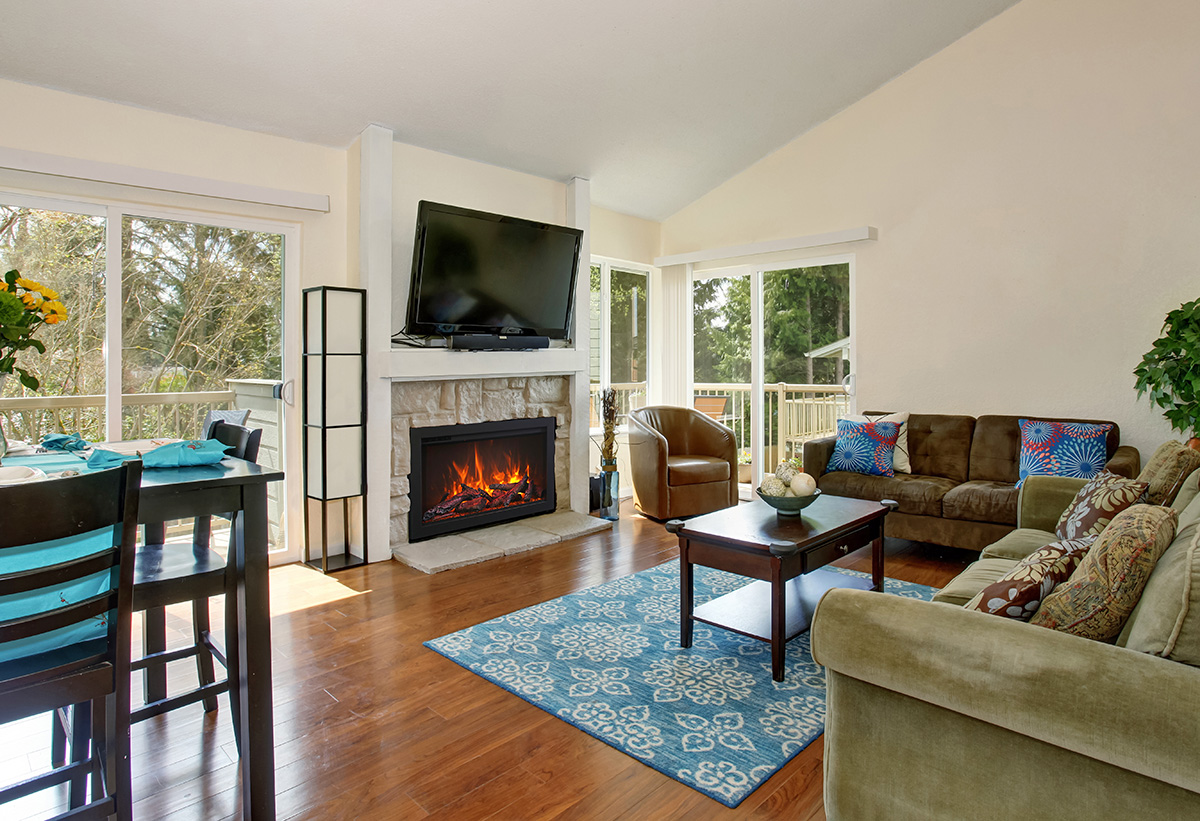 Excellent living room with blue rug and fireplace.